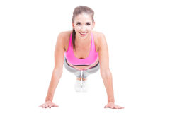 Fit woman doing push-up and smiling. Isolated on white background stock image