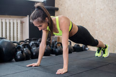 Fit woman doing push-ups on the floor, sporty female working out abs, arm muscles royalty free stock images
