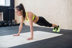 Fit woman doing push-ups on the floor, sporty female working out abs, arm muscles royalty free stock photo