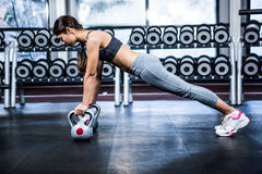 Fit woman doing push ups with kettlebells Royalty Free Stock Image