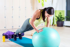 Fit woman doing push ups with medicine ball. Workout out arms Exercise training triceps and pectorals muscles Royalty Free Stock Image