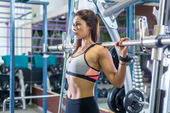 Fit woman doing shoulder press exercise with a weight bar Smith machine at gym. Fit woman doing shoulder press exercise with a weight bar Smith machine at gym stock photos