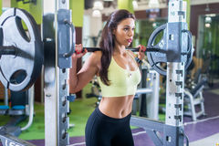 Fit woman doing shoulder press exercise with a weight bar Smith machine at gym. Fit woman doing shoulder press exercise with a weight bar Smith machine at gym royalty free stock image