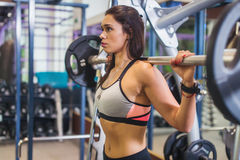 Fit woman doing shoulder press exercise with a weight bar Smith machine at gym. Fit woman doing shoulder press exercise with a weight bar Smith machine at gym royalty free stock images