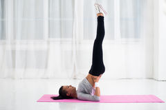 Fit woman doing shoulder stand on mat practising. Yoga health and fitness concept stock photo