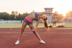 Fit woman doing side bend stretching exercise warming up. Stock Image