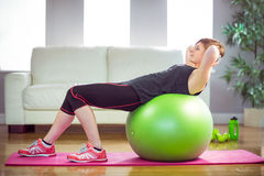 Fit woman doing sit ups on exercise ball. At home in the living room Stock Photo