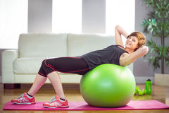 Fit woman doing sit ups on exercise ball Stock Photos