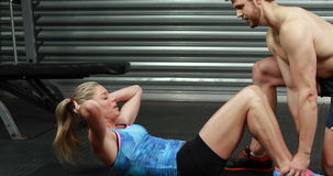 Fit woman doing sit ups with trainer. At the gym stock video