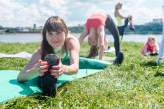 Fit woman doing splits on mat in nature, stretching her legs. Group training outdoors. Royalty Free Stock Image
