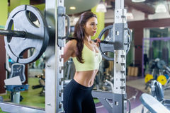 Fit woman doing squats with the barbell Smith machine in the gym. Stock Photos