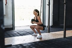 Fit woman doing squats with kettlebell in sport club. Side view Royalty Free Stock Photos