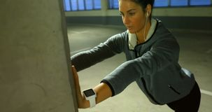 Fit woman doing stretching exercise 4k. Fit woman doing stretching exercise in underground parking area 4k stock video footage
