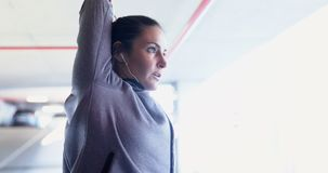 Fit woman doing stretching exercise 4k. Fit woman doing stretching exercise in underground parking area 4k stock footage