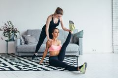 Fit woman doing stretching exercises with the help of friend holding her leg at home. Fit women doing stretching exercises with the help of friend holding her Stock Photo