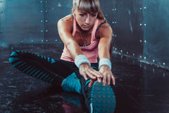 Fit woman doing stretching exercises her muscles Stock Photography