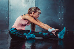 Fit woman doing stretching exercises her muscles back and legs before a training warm up at gym concept fitness, sport Royalty Free Stock Image