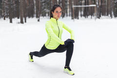 Fit woman doing stretching exercises before running outdoors looking at camera Winter street training Royalty Free Stock Image
