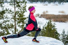 Fit woman doing stretching exercises before running outdoors. Winter street training. Stock Photos