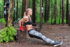 Free Fit Woman Doing Triceps Dips At Park. Fitness Girl Exercising Outdoors With Own Bodyweight Stock Photo - 74550740