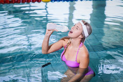 Fit woman doing underwater bike and drinking water Royalty Free Stock Photo