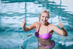 Fit woman doing underwater bike with thumbs up Stock Photography