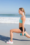 Fit woman doing weighted lunges on the beach Stock Images