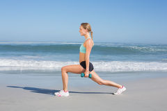 Fit woman doing weighted lunges on the beach Royalty Free Stock Images