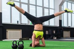 Fit woman doing yoga exercise, headstand in gym. royalty free stock images