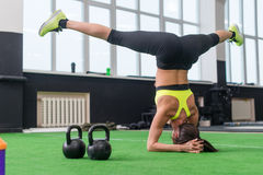 Fit woman doing yoga exercise, headstand in gym. Stock Photography