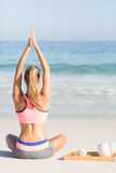 Fit woman doing yoga beside the sea Stock Photo
