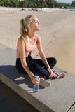 Fit woman dressed in tracksuit taking break after sport activities outdoors Royalty Free Stock Photos