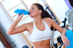 Fit woman drinking in gym. Fit woman with energy drink relaxing and drinking in the gym Royalty Free Stock Photos