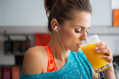 Fit woman drinking pumpkin smoothie in kitchen Stock Photography
