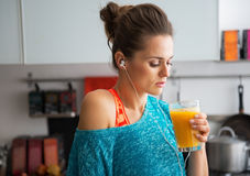 Fit woman drinking pumpkin smoothie in kitchen Stock Image