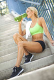 Fit woman drinking sports bottle on steps. A fit, attractive female drinking from a sports bottle on steps Royalty Free Stock Photos