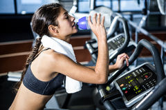 Fit woman drinking water while doing bike exercise Royalty Free Stock Photography