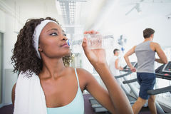 Fit woman drinking water beside treadmills Royalty Free Stock Images