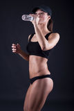 Fit  woman drinking water after workout on black background Royalty Free Stock Image