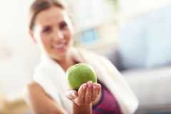 Fit woman eating carrot at home Royalty Free Stock Photo