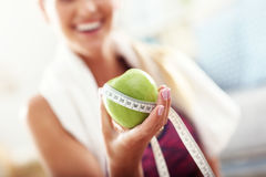 Fit woman eating carrot at home Royalty Free Stock Photos