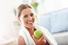 Fit woman eating carrot at home Stock Photography