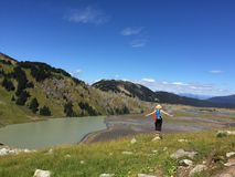 Fit Woman Enjoying Veiw of Alpine Lake Surrounded with Mountains. Stock Image
