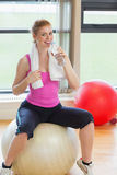 Fit woman on exercise ball with water bottle Stock Image