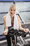 Fit woman on exercise bike Royalty Free Stock Photos
