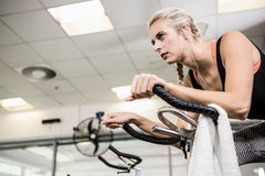 Fit woman on exercise bike. At the gym Royalty Free Stock Photography