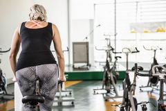 Fit woman on exercise bike. At the gym Stock Photography