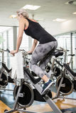 Fit woman on exercise bike. At the gym Stock Images