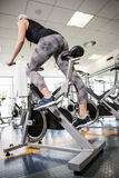 Fit woman on exercise bike. At the gym Royalty Free Stock Photo