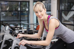 Fit woman on exercise bike. At the gym Royalty Free Stock Image